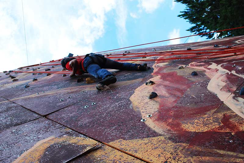 Laina no desafiando às alturas na escalada