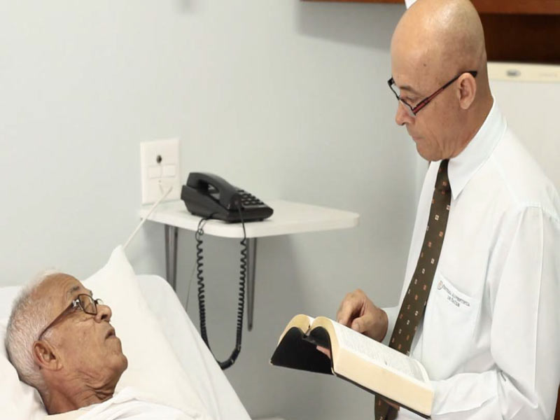 Capelão orando com paciente