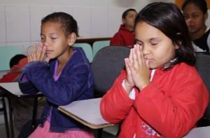Crianças orando na Escola Cristã de Férias