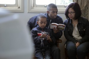 Família lê a Bíblia durante o culto da equipe modelo. Comunhão com Deus foi essencial para o trabalho