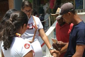 Jovens oram com moradores durante projeto