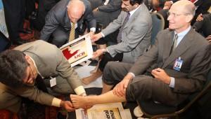 Pr. Magdiel Perez, secretário sul-americano adventista, pinta o pé do líder mundial, Pr. Ted Wilson