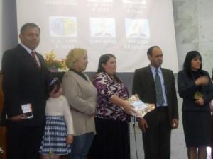 À esquerda, pastor Yuri Quintana, ao lado da pequena Isabella, filha de Eliane, em momento de entrega de certificado de batismo