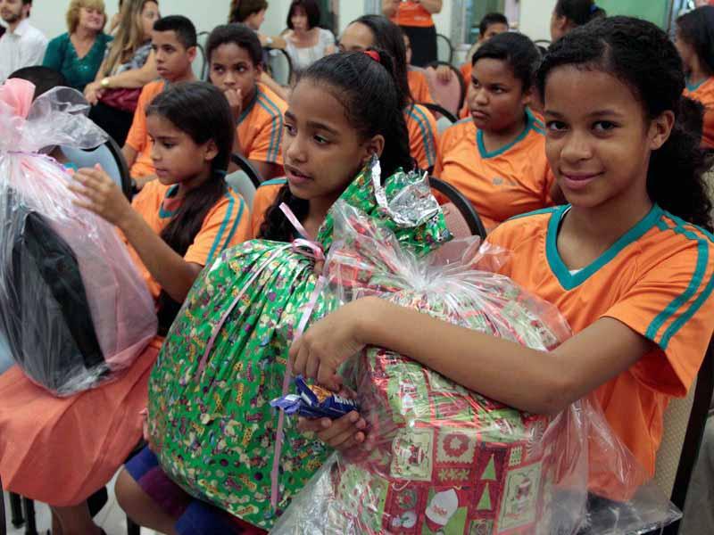 Crianças do núcleo de Helena Maria sorriem ao receberem os presentes de natal