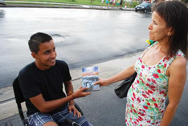 Morador da região de Peruíbe recebendo o livro