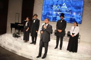 Pastor Erton fala e, ao fundo, funcionários vestidos tal como pioneiros adventistas