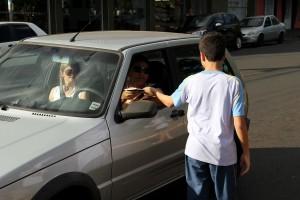 Alunos da escola adventista espera o sinal fechar para entregar livro para motorista.