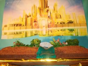 O formato do bolo foi a Cidade Santa encima de um livro aberto.