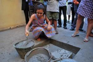 Futura aluna ajuda a concretar a pedra fundamental