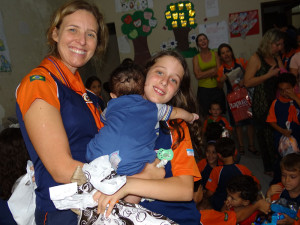 Secretária Isabela e a aventureira Milena, 9 anos, entregam o kit de presentes ao bebê de quatro meses, morador da Casa de Acolhimento Infantil, em comemoração ao Dia das Crianças