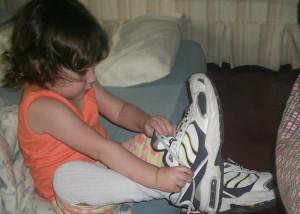 Ana Julia colocando o tênis do pai