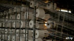 Rolos separados formam um emaranhado de fios. Dessa aparente bagunça sai um tecido uniforme